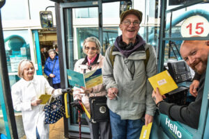 The driver on the bus handing cards to Right to left TerenceBlackadder -real name- Christine Hubbard and Annette Pencheon